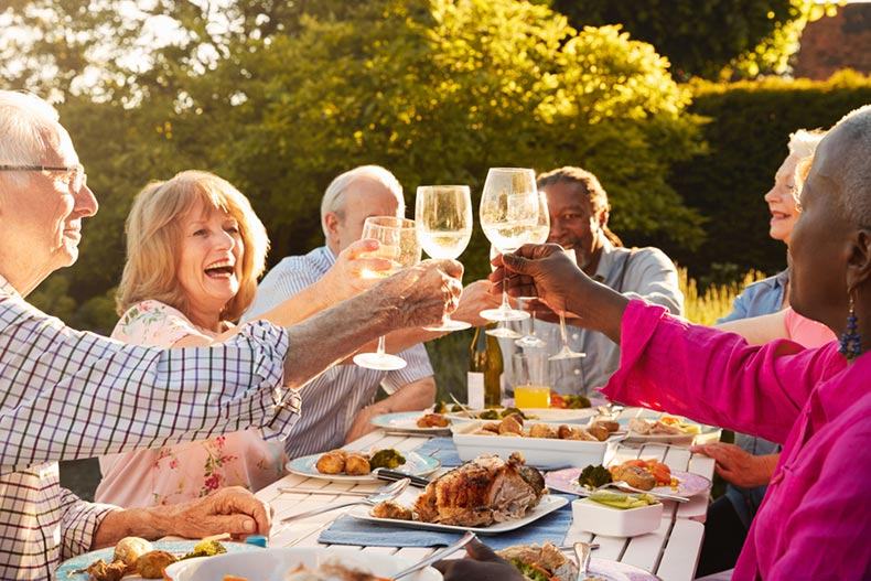 A group of older adults smiling while toasting with wine glasses and eating dinner at a picnic table