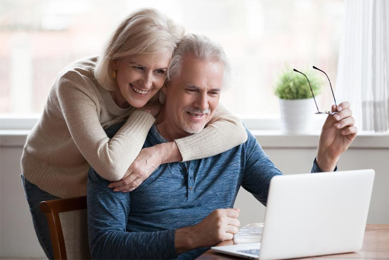 Senior couple smiling while using laptop together