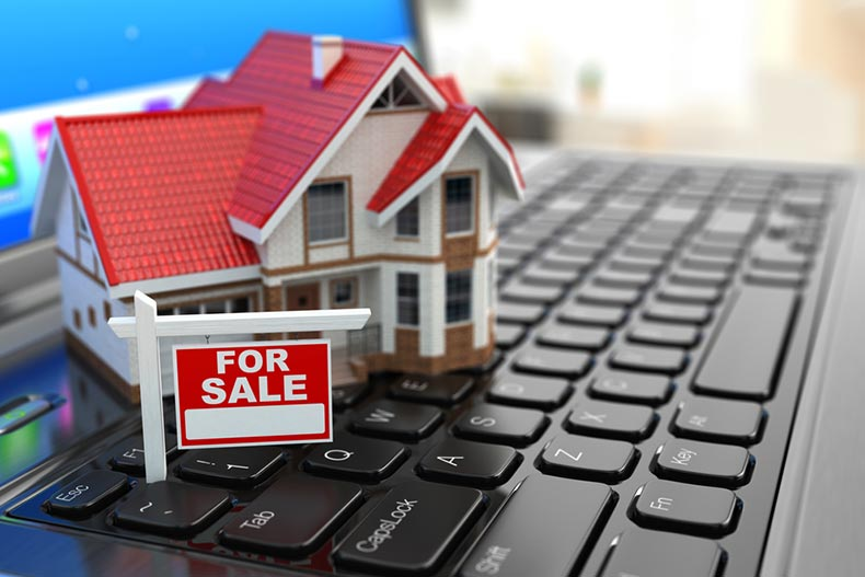 "A small, model house with a ""For Sale"" sign sitting on top of a laptop keyboard"