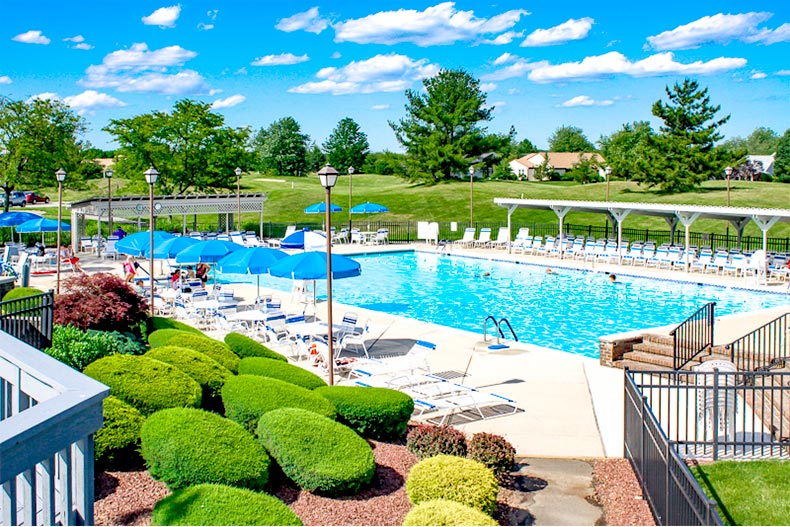View of the outdoor pool, patio, and greenspace at Concordia in Monroe, New Jersey
