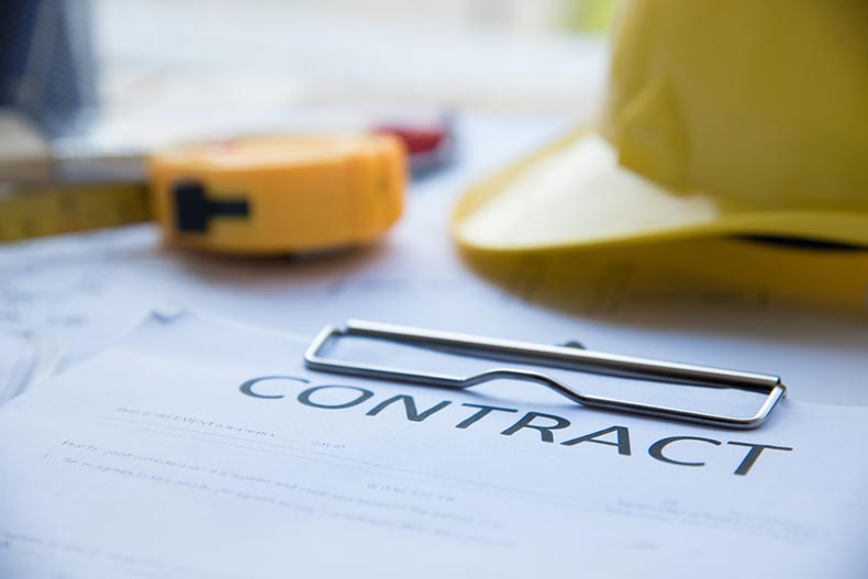 A hard hat and tape measure on a clipboard with a contract