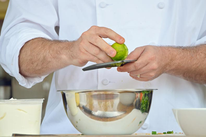 Closeup on the hands of a chef as he puts lime zest into a stainless steel bowl during an online cooking demo