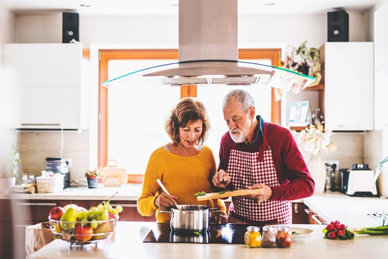 Older couple cooking over a stove in modern kitchen
