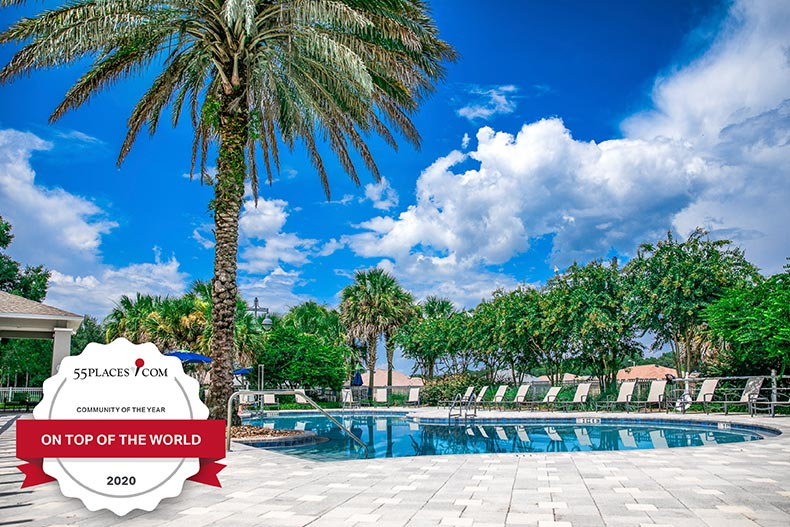 """Community of the Year"" badge over an outdoor resort-style pool at On Top of the World in Ocala, Florida"