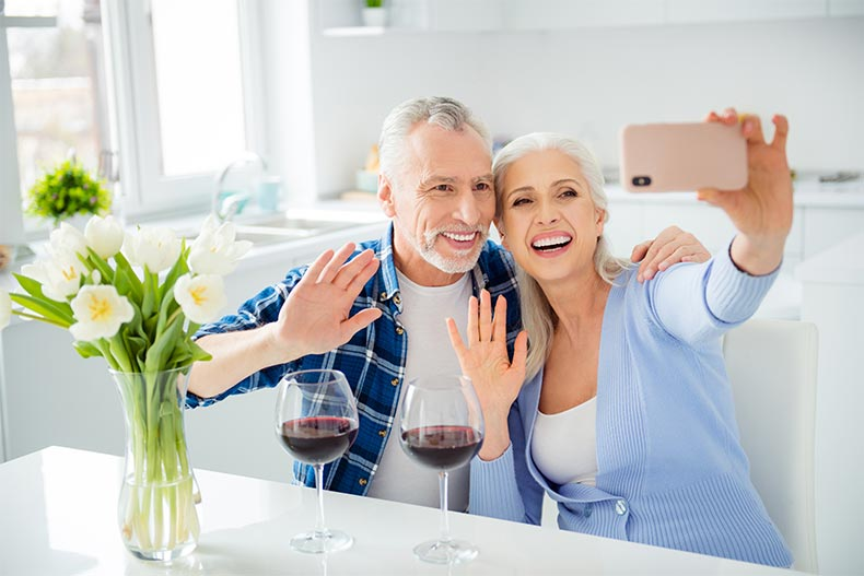 An older couple drinking wine and waving at a smart phone screen