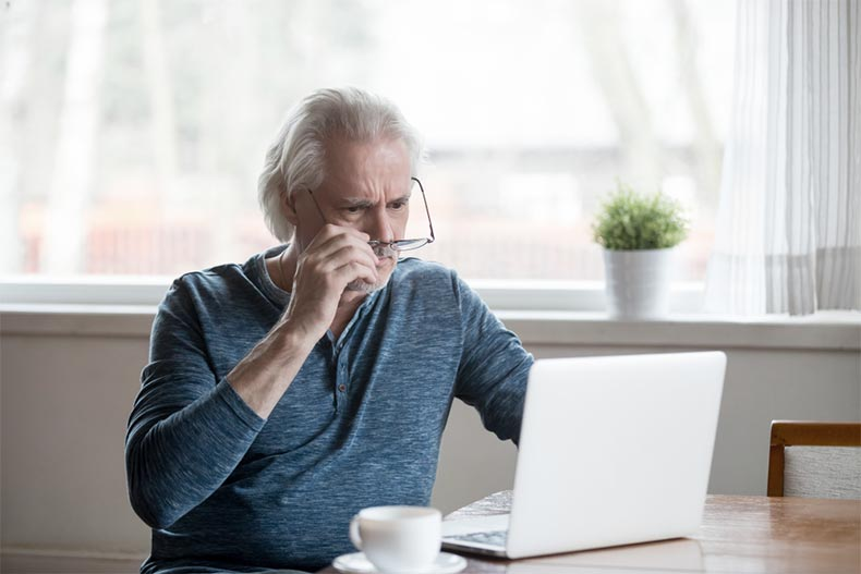 An older man sitting at a table and lowering his glasses as he skeptically looks at his laptop