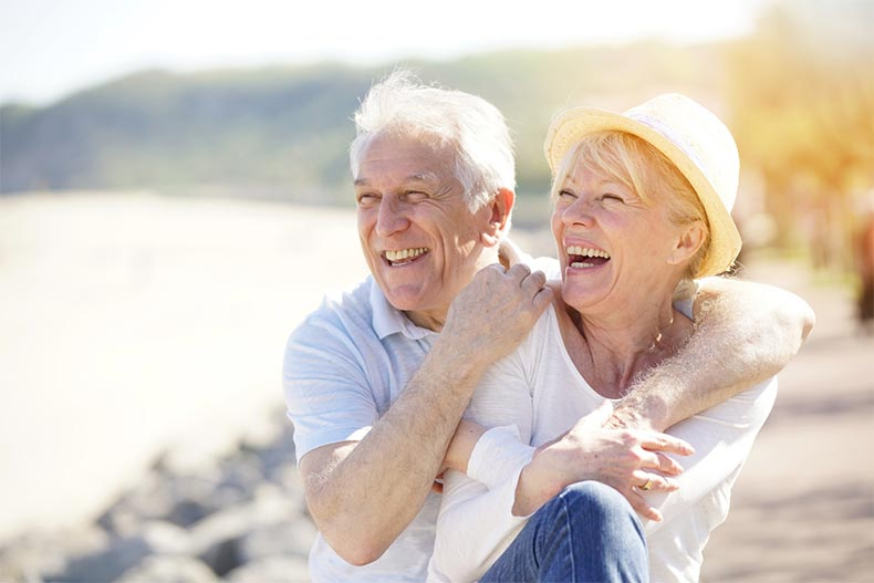 A senior couple with their arms around each other smiling and laughing while on a beach