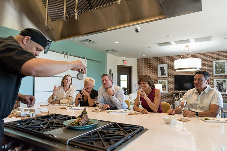 A group of residents enjoying a cooking demonstration in the community kitchen at Trilogy at Ocala Preserve in Ocala, Florida
