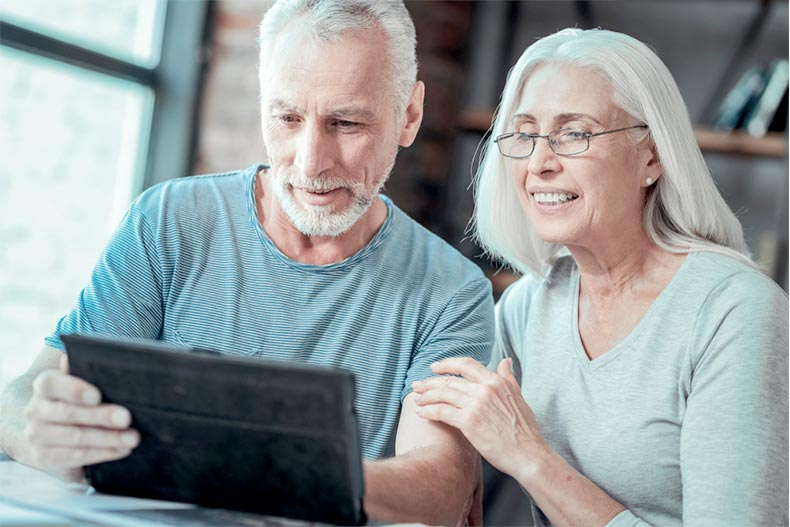 An active adult couple looking at a tablet