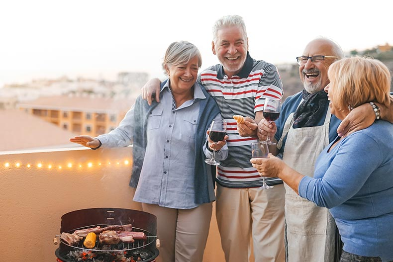 Active adult friends laughing while enjoying wine and a barbecue on a balcony