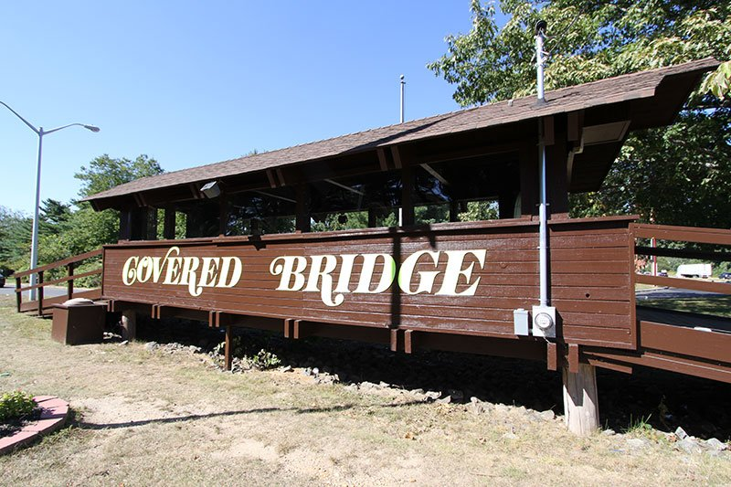 Wooden Bridge with sign for community called Covered Bridge