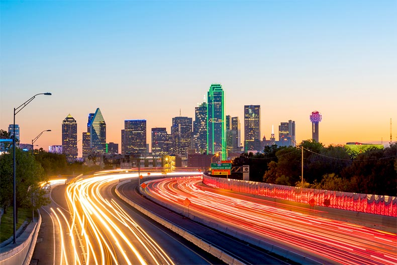 Sunset view of a highway leading to downtown skyline of Dallas, Texas