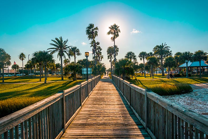 Photo of a fishing pier with palm trees surrounding it at sunset in Daytona Beach, Florida