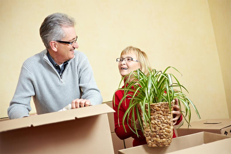 An older couple smiling at each other while packing moving boxes