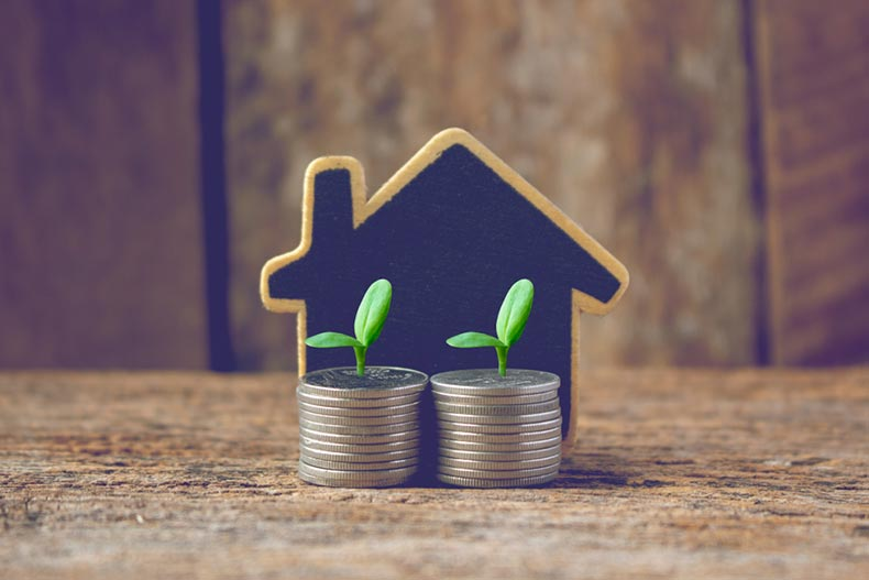The silhouette of a house behind two stacks of coins with sprouts growing out of them