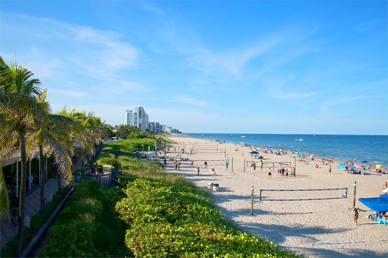 North side of Deerfield Beach in Florida with beachgoers sunbathing and enjoying water activities
