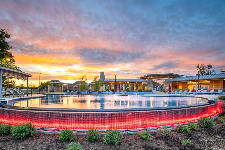Sunset view of the outdoor pool at Del Webb at Trinity Falls in McKinney, Texas