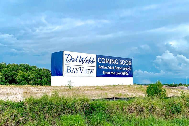 "Greenery surrounding the ""Coming Soon"" sign for Del Webb BayView in Palmetto, Florida"