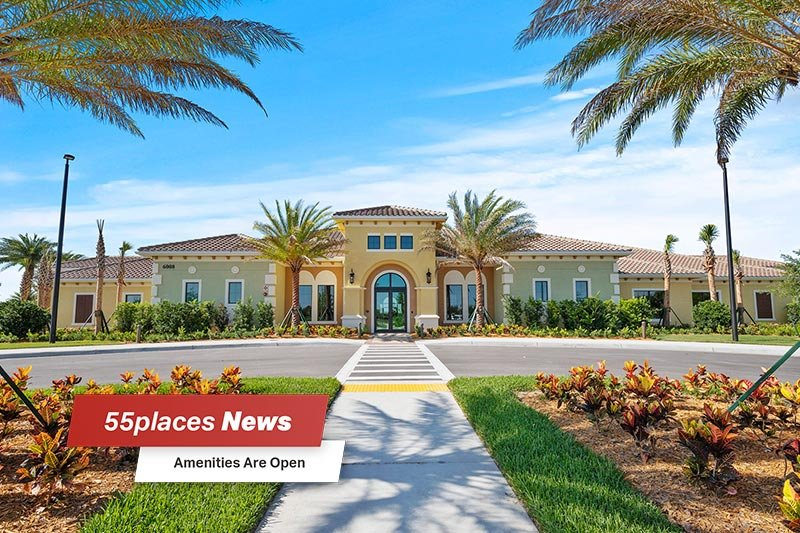 """55places News: Amenities Are Open"" banner over exterior view of the Grand Hall Clubhouse at Del Webb Naples in Ave Maria, Florida"