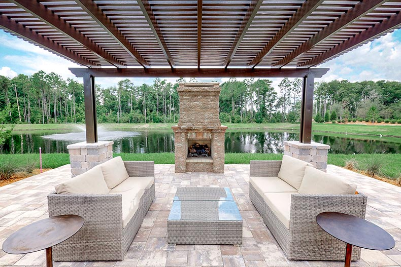 An outdoor patio and fireplace beside a pond at Del Webb Nocatee in Ponte Vedra, Florida