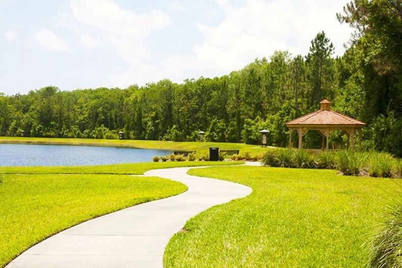 A picturesque pond, gazebo, and pathway on the grounds of Del Webb Ponte Vedra in Ponte Vedra, Florida