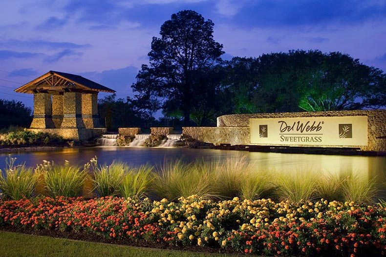 A nighttime view of the pond and greenery surrounding the community sign for Del Webb Sweetgrass in Richmond, Texas