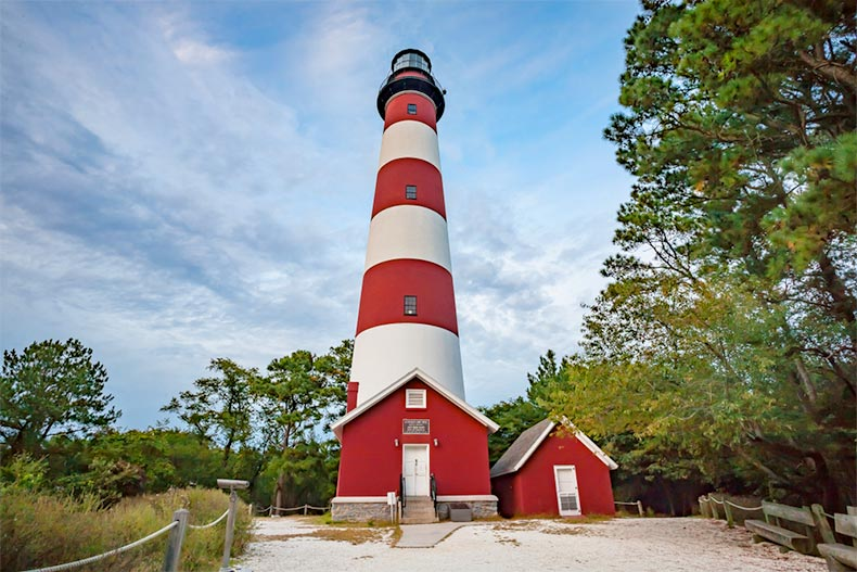 A blue sky and clouds over a red and white striped lighthouse on the Delmarva Peninsula, Virginia