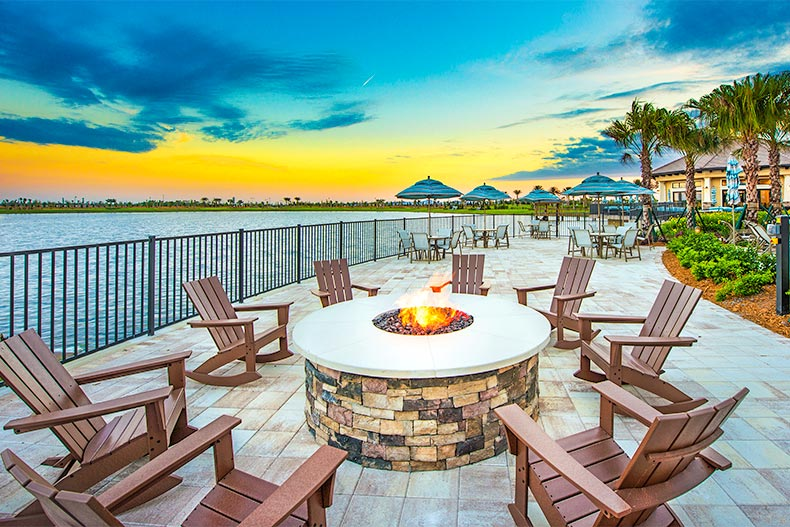 Chairs around a fire pit near water and a sunset in Del Webb Lakewood Ranch