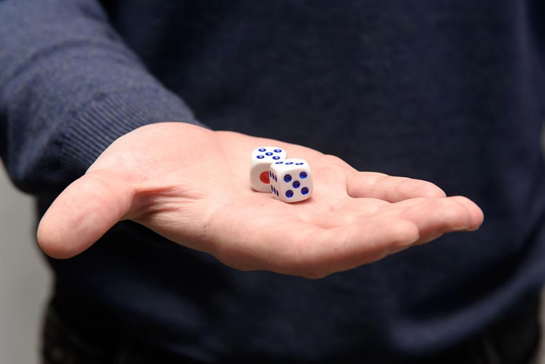 A man's hand holding two dice blocks