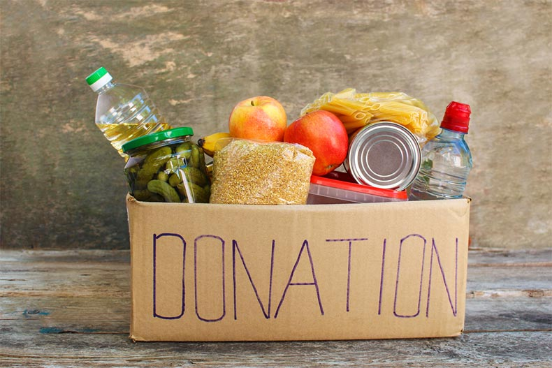 A cardboard donation box with food on a wooden floor