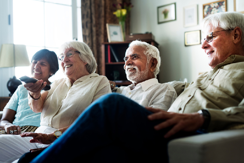 group of senior adults laughing on couch together in community home