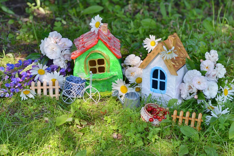 Two miniature houses with garden flowers and summer berries