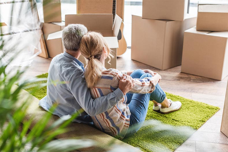 An active adult couple embracing while sitting on carpet and downsizing into a new house