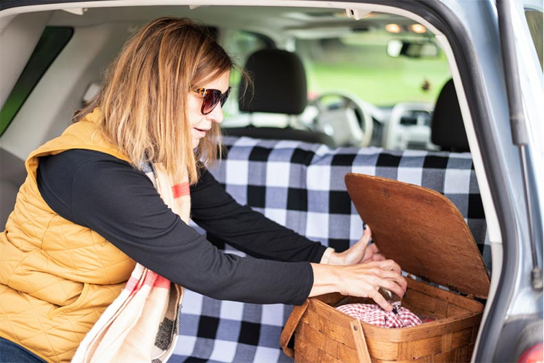 An older woman packing a picnic basket in the back of a car for a road trip