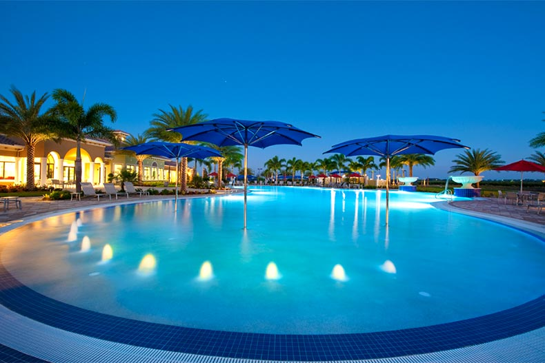 Zero-entry pool with umbrellas in Del Webb Naples at night