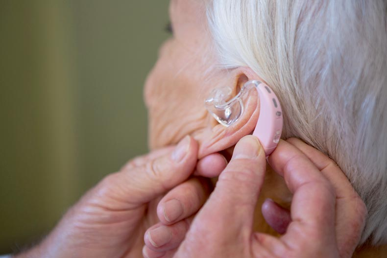 Doctor fitting a hearing aid on a senior patient's ear