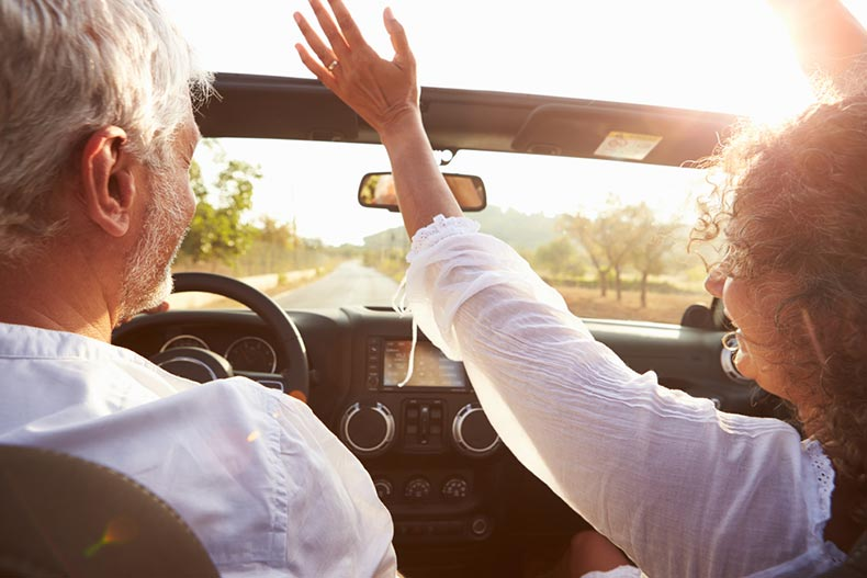 An active adult couple driving in a convertible and enjoying their early retirement