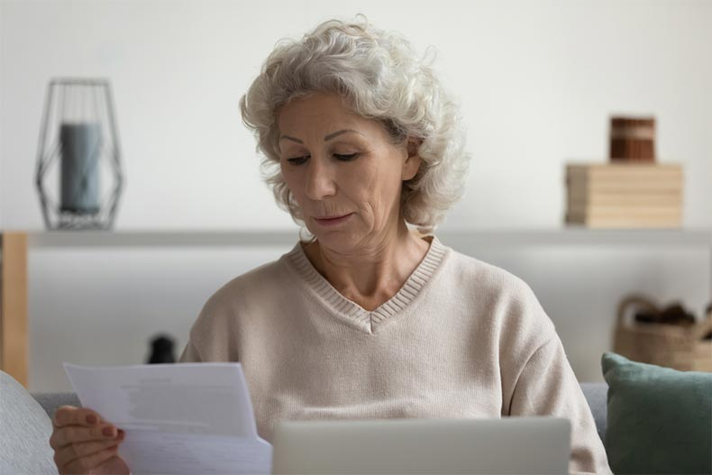 An older woman inspecting a suspicious document and researching it on her laptop