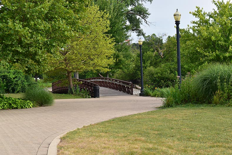 Greenery surrounding a picturesque cobblestone path and bridge in a park in Downtown Elgin, Illinois