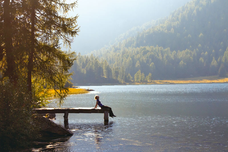 person out in forest sitting on dock of lake