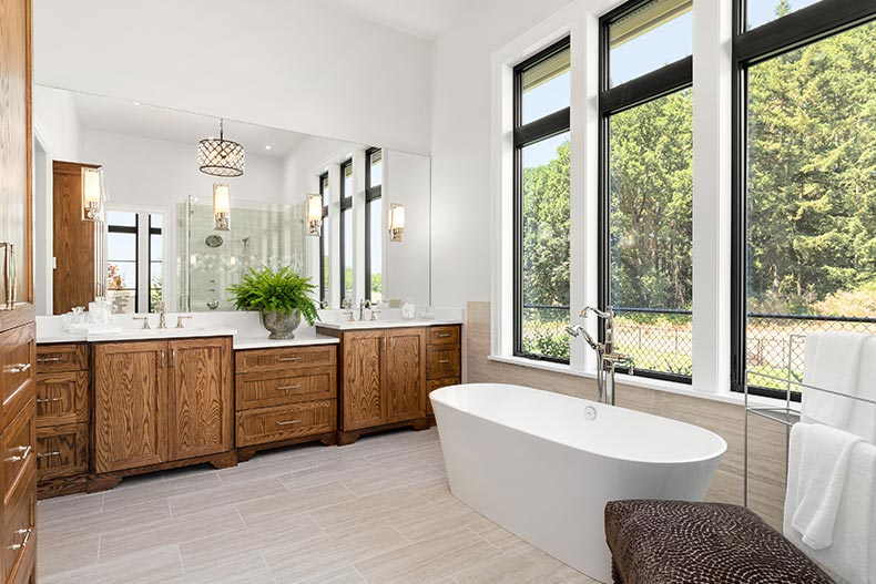 An en suite bathroom with hardwood cabinets and a freestanding bathtub in a new luxury home
