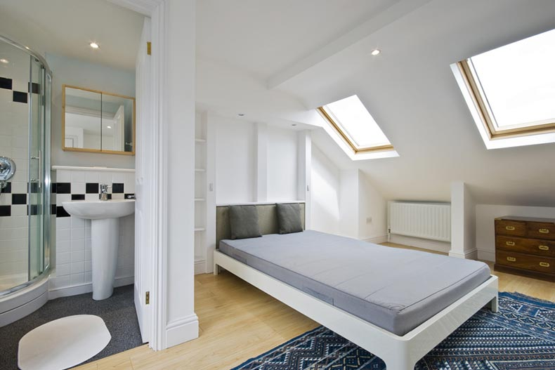 A loft bedroom with en suite bathroom and skylight windows