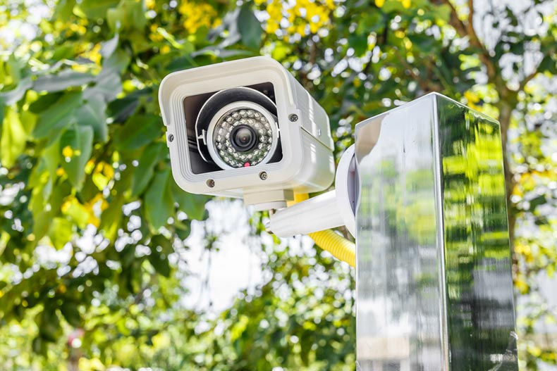 A white home security camera with tree branches behind it