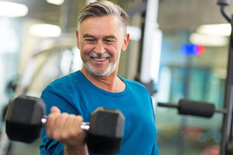 An older man smiling while lifting a dumbbell in a community fitness center
