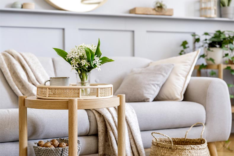 A living room with a sofa, a wooden coffee table, spring flowers in vase, and elegant personal accessories