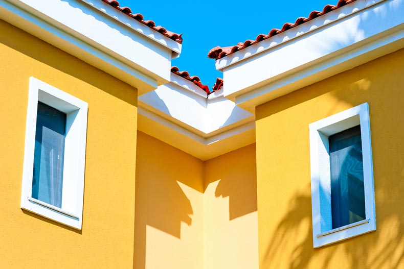 Two windows in a house painted bright yellow
