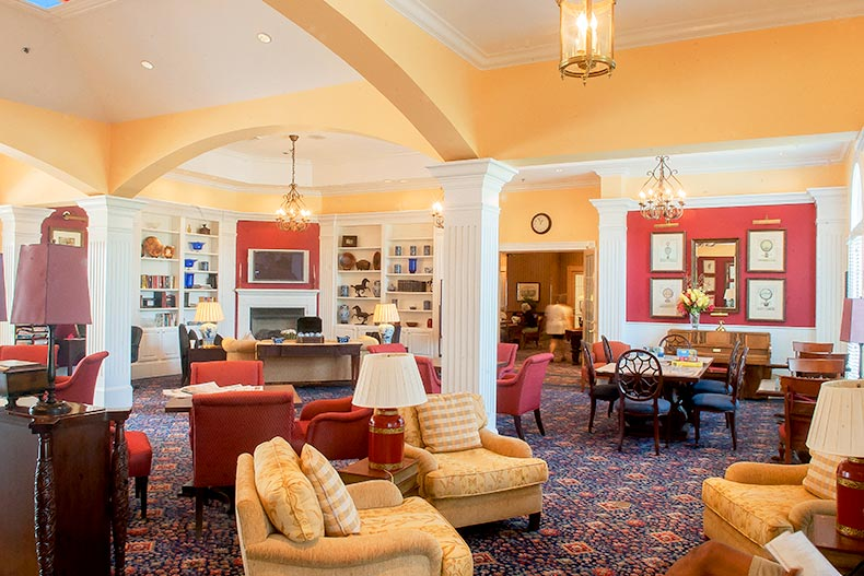 View of the tables and couches in the warm interior of the clubhouse at Falls Run in Fredericksburg, Virginia