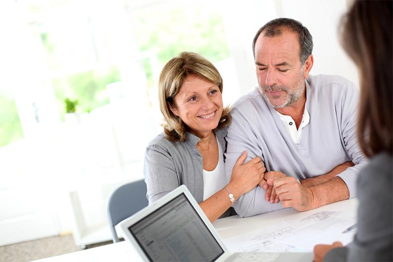 A senior couple meeting with a real estate agent to find a home in an active adult community