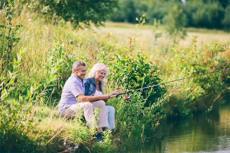 A senior couple fishing on the banks of a river