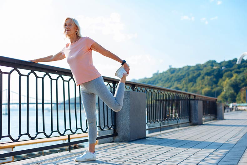 Older, athletic woman pausing to stretch her leg while running across a bridge